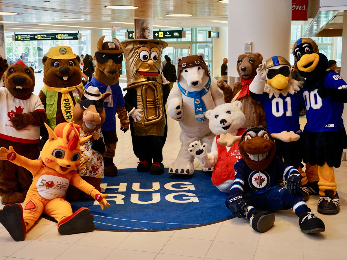 A warm welcome - Winnipeg Mascots welcoming passengers on the hugrug during tourism week